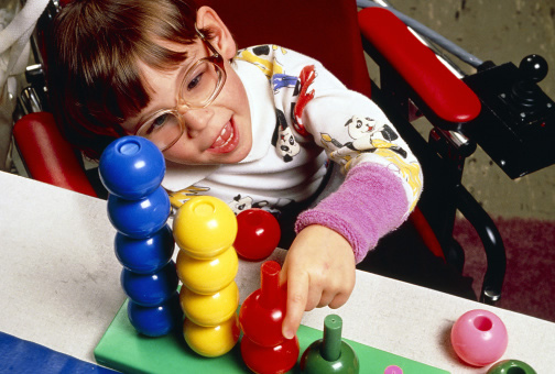 a handicapped child playing with a toy