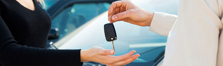 dealer handing keys to new car