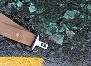 a seat belt on the road surrounded by broken glass