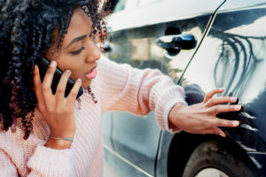 woman-on-phone-touching-car-scratch